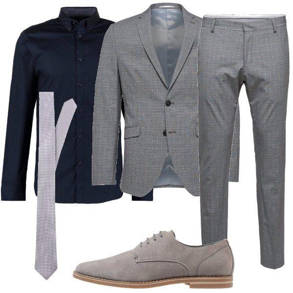 Un look elegante e adottato da un uomo con stile, che vede: camicia color blu scuro, in cotone, completo composto da giacca e pantalone grigio, stringate grigie in fintapelle, ad effetto scamosciato e cravatta grigia.