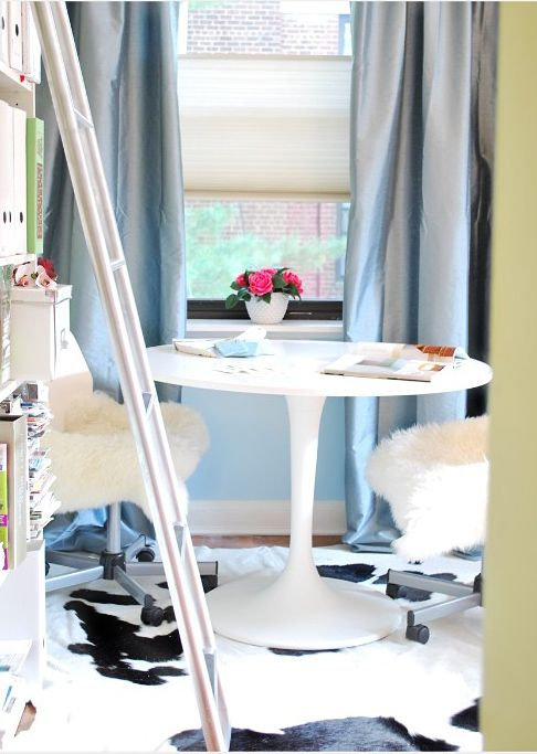 Chic blue & green office design with green walls paint color, blue silk curtains, white Ikea Docksta table, white swivel office chairs, white & black cowhide rug, white, bookcase and ladder.