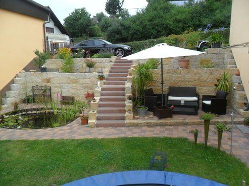 Richtig cool: eine Steinterrasse am Hang. So kann man einen Hanggarten perfekt ausnutzen!