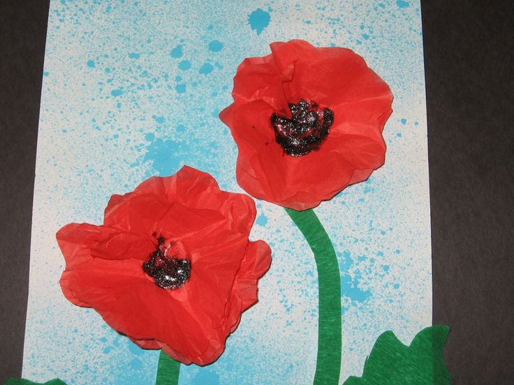 Poppies, Remembrance Day, 4-layer tissue paper, black glitter glue centre, crepe paper leaves, stem on blue food colouring sprayed paper
