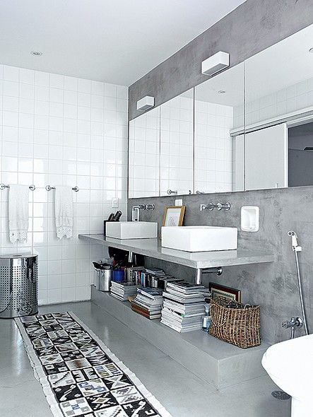 Criado no recuo lateral, o banheiro do casal tem bancada de concreto, com duas cubas de apoio, e portas de correr com caixilho de alumínio e vidro temperado fosco que dão acesso a um terraço. Projeto de Claudia Haguiara