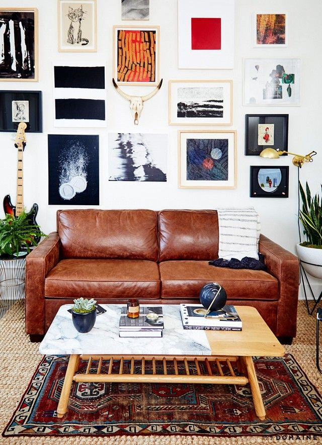 Eclectic living room with a large gallery wall, a leather sofa, a marble coffee table, layered rugs, and potted plants