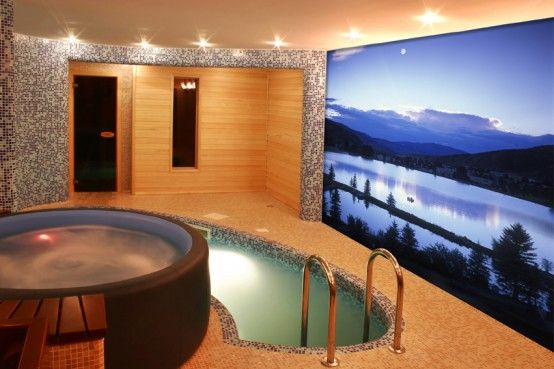A indoor pool with a television on the wall - wouldn't I love that!