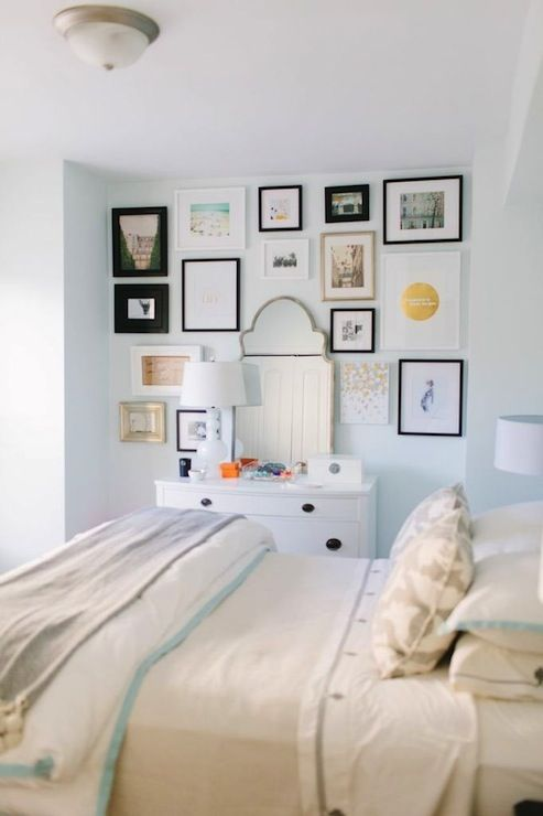 source: The Every Girl Danielle Moss - Breakfast at Toast - Chic bedroom with watery green paint, Farrow & ball Cabbage White, with Wisteria Antiqued Moroccan Mirror surrounded by eclectic art gallery over white dresser filled with white milk glass lamp. Queen bed is filled with Serena & Lily Aqua Border Frame Duvet & Shams, Serena & Lily Pewter Gobi Embroidered Sheet Set and Serena & Lily Navy Pom Pom throw