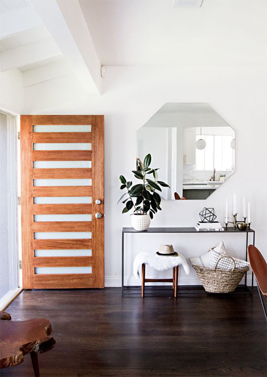 Modern minimalist home. Wood & glass front door. Entry console table. Hexagon mirror.