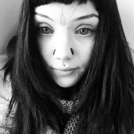 The beautiful Grace Neutral with her scarred forehead and cheeks, scalpeled nostrils, philtrum piercing, and tattooed eyeballs.