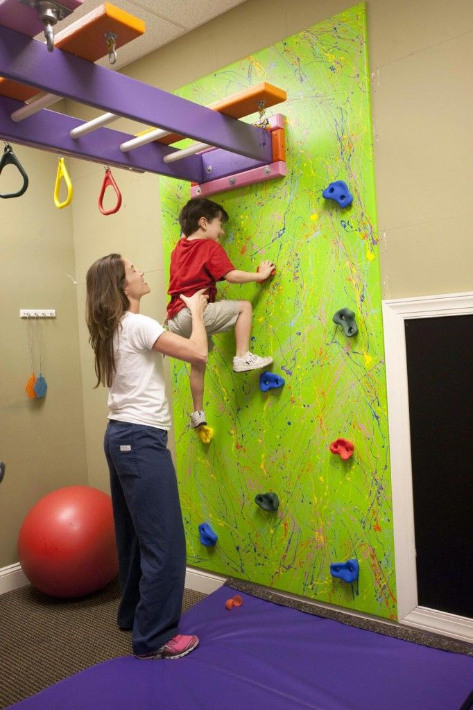 A climbing wall with monkey bars above.