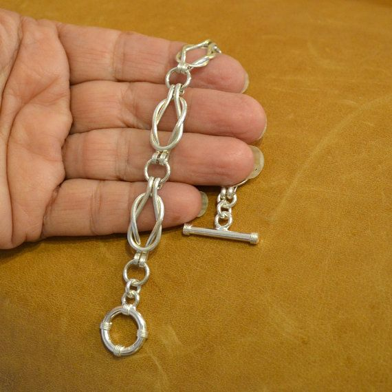 Call it Sailors Knot or Love knot - this linked Sterling Silver bracelet is entirely handmade by me. It drapes beautifully and comfortably across your wrist. Each link including the connecting rings begins as a piece of wire which is then measured, cut and shaped by hand. The bracelet uses no solder to construct it. Size 7 (approximately 18cm) is average for a woman. There is just over 1/4 oz of solid Sterling Silver in the bracelet.  please put an alternate size in the notes to seller on…