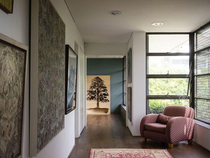 VILLA SULLA BAIA DI SYDNEY - LA GALLERIA D'ARTE Una poltrona in stile retrò che i proprietari hanno fatto restaurare guarda la parete attrezzata che ospita la collezione di dipinti. Una griglia in maglia di ottone filtra la luce.