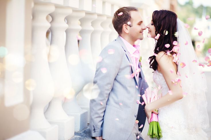 Just married couple kissing with pink flower petals
