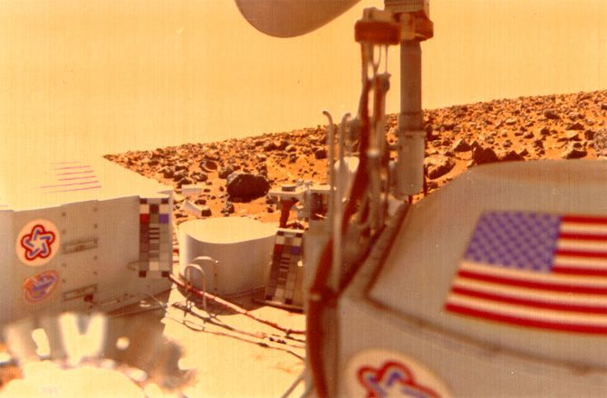 This view from Viking 2 was snapped on Nov. 2, 1976, showing a part of the lander's deck, the American flag, the bottom of the robot's high-gain antenna and a boulder-littered Utopia Planitia, the largest identified impact crater on Mars.