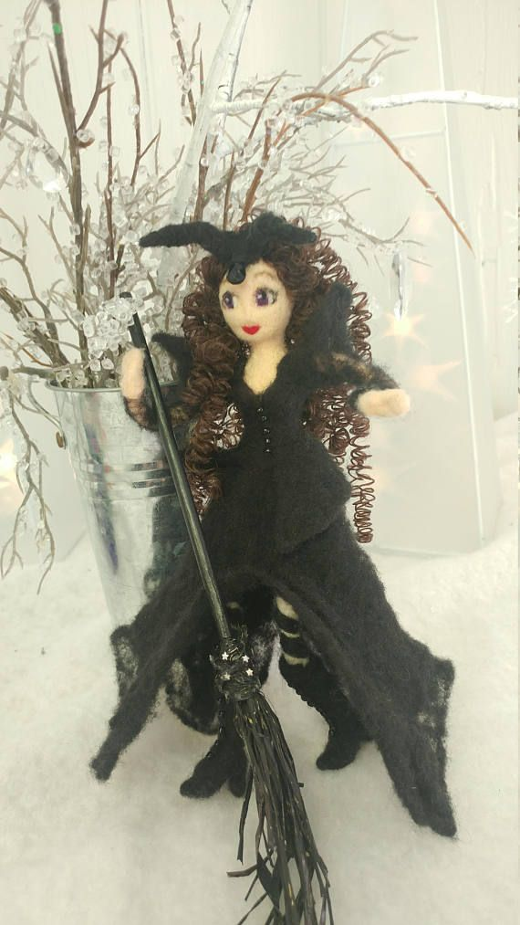 A beautiful brown haired, violet eyed kitchen witch Sorceress has ruby-red lips and is dressed in her witchiest finery and maleficent type headdress. Her wool lace-trimmed skirt has v slits in the front and back. The black beaded over-blouse has a peplum bottom, and poofed pointy