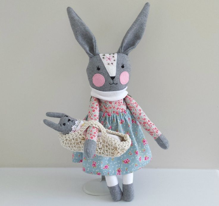 This one of a kind handmade bunny rabbit doll is named Emilia and she has her own baby bunny in a Moses basket.She measures approximately 37 cm (14.5 inches) tall from top of head or 46 cm (18 inch) tall from tip of ears to toes.The baby bunny measures approximately 17 cm (6.5 inch) tall and her bodice matches her mummy. The basket has a blanket and embroidered sheet to keep bunny snug.Her tail is soft and furry and so is the baby's tail!She wears a removable elasticat...
