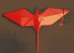 Colocando el dragón boca arriba debe tener la misma forma que la figura de la derecha.     A continuación, doblamos un ala hacia abajo de manera perpendicular tal como indica la flecha