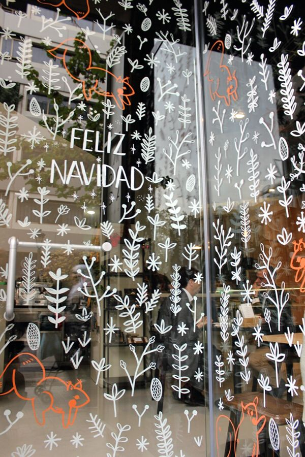 Boutiquizing Inspo: We all love those famous icons of Christmas: snow, fir trees, squirrels. This lovingly-detailed piece makes extensive use of adorable tiny drawings to create a characterful and impressive window display, cute little tree rats and all.  Trendwatch: Liquid chalk markers \ White \ Calligraphy \ Window art \ Christmas & Winter. Artwork by Gisela Talita.