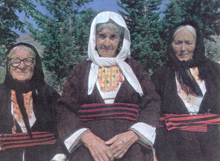 Older ladies from Tilos in their everyday life (under) dress with little embroidery, the poukamiso. Outside the house she wears over it a woolen dress from handspun and woven sheep wool. Their Trachilia is colorful embroidered and has a typical triangular pattern.