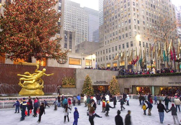 Outdoor Ice Skating in New York City. You can see the Christmas Tree at Rockerfeller Center in the background.