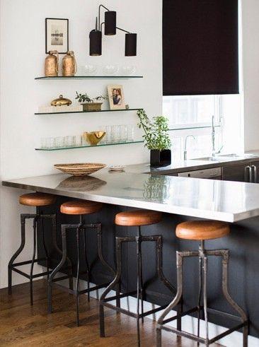 Sleek kitchen design with glass open shelving and rustic bar stools | Nate Berkus Interiors