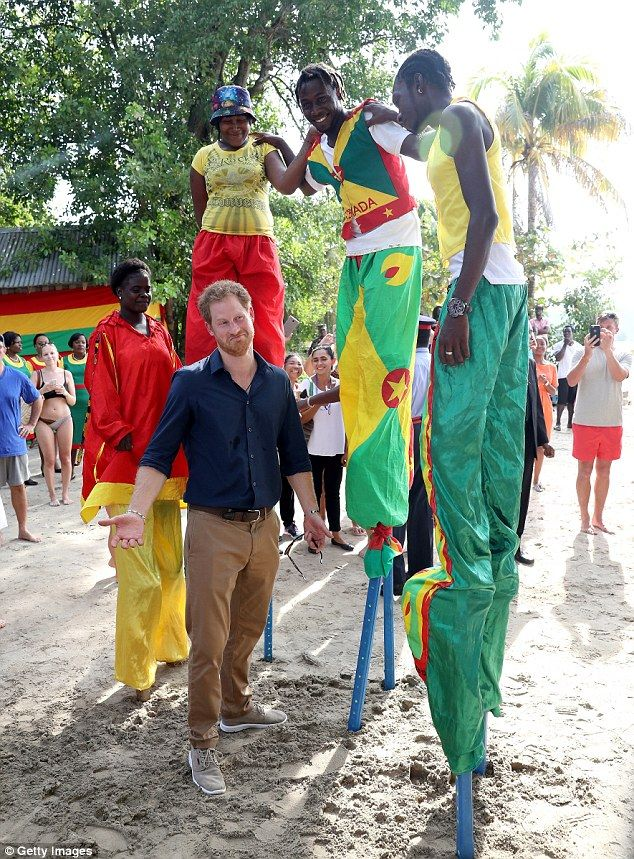 Prince Harry meets stilt walkers on the eighth day of an official visit to Grand Anse Beac...