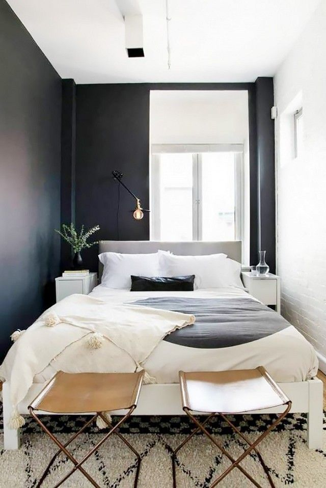 Small Swedish Inspired Bedroom With Black Walls Simple Bedding And Leather Stools