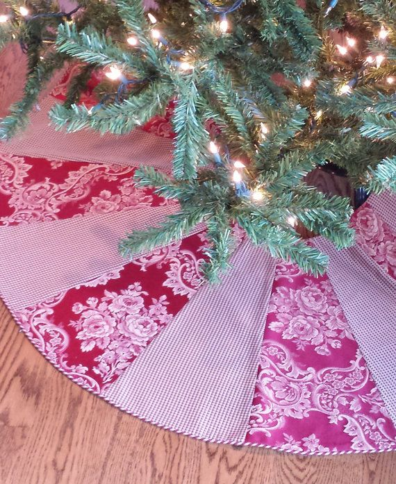 This 50 Christmas Tree Skirt has alternating damask/jacquard and checked panels. Maraschino cherry red and wheat/gold fabric is finished in a red/gold swirl piping. The 10 opening will sit nicely over your tree stand and will allow you to easily water your real tree. It is fully lined.