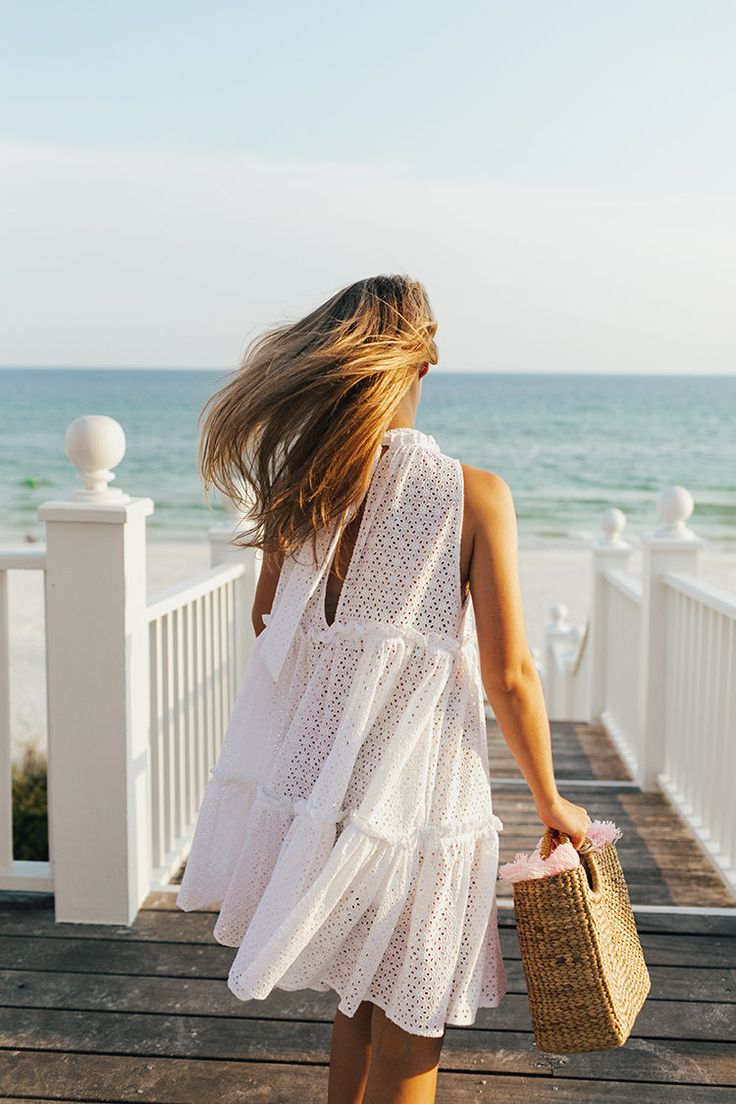 White broderie anglaise dress and straw bag by the seaside.