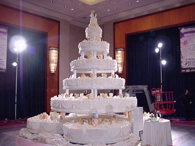 "I found this by googling ""Biggest Wedding cake in the world""  there's no people, but for a size reference, that thing that looks like a cake in the front is actually a table, and there is a forklift if the back"