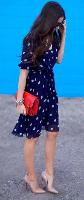 Navy and white polka dot dress with red clutch and heels