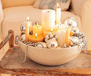 Shabby chic coffee table decor with extra candles, glass ornaments and garland. Tip give the candles a stable base by first by filling the bottom of the bowl with sand or small craft pebbles. Then add the ornaments/garland around them.