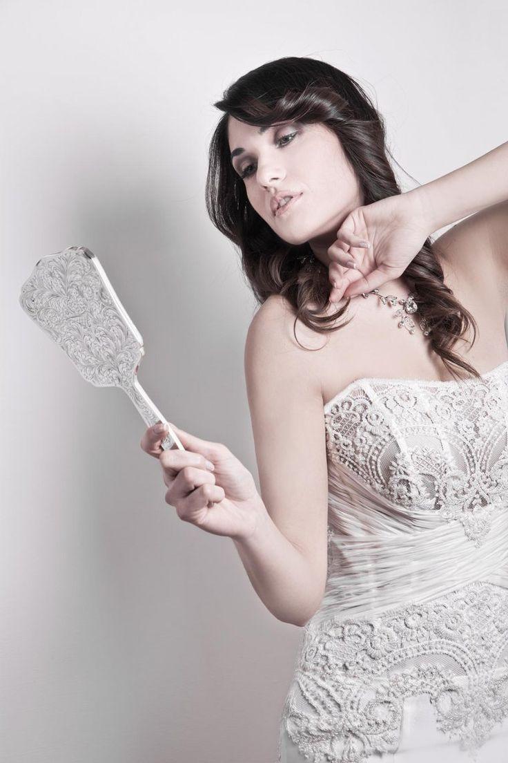Il luccichio di micro cristalli si miscelano con la greca di pizzo chantilly francese, chiffon plissettato e incrociato che adornano la struttura del corsetto con giochi di trasparenze che si completano con la gonna a sirena di satin.
