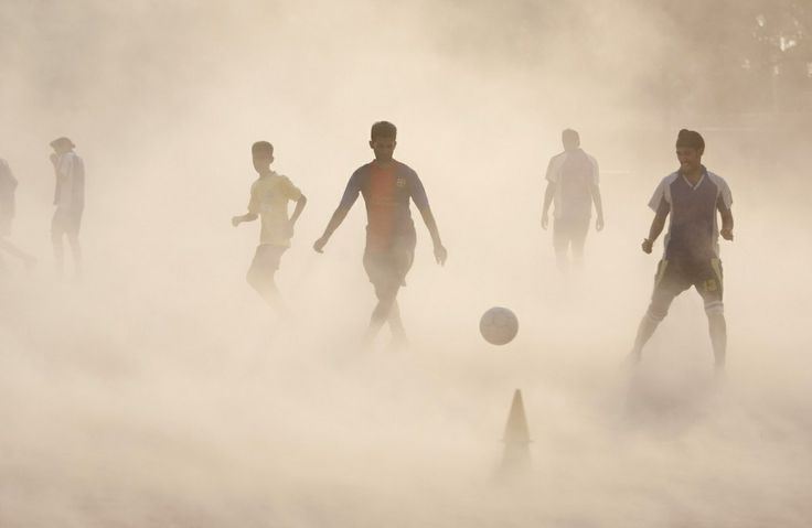 Aspiring young Indian soccer players continue with their practice during a dust storm in Jammu, India, Wednesday, June 11, 2014. Soccer fans around the world are gearing up to watch the Soccer World Cup that begins in Brazil Thursday. (AP Photo/Channi Anand)