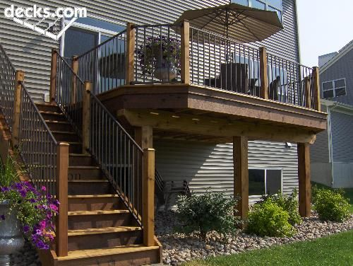 This description of a Second story, elevated deck designed with angled corners, slim decorative balusters and stone landscaping below tumbling out to fire pit and wall would make me very happy if I owned a house with this situation!!
