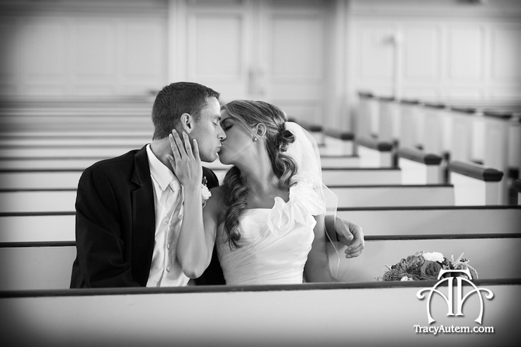 bride and groom sharing a kiss in a pew at the Robert Carr Chapel. Photographed by Tracy Autem Photography. http://tracyautem.com