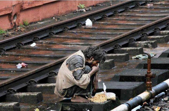 2. A homeless and hungry man eats off a railway track in India