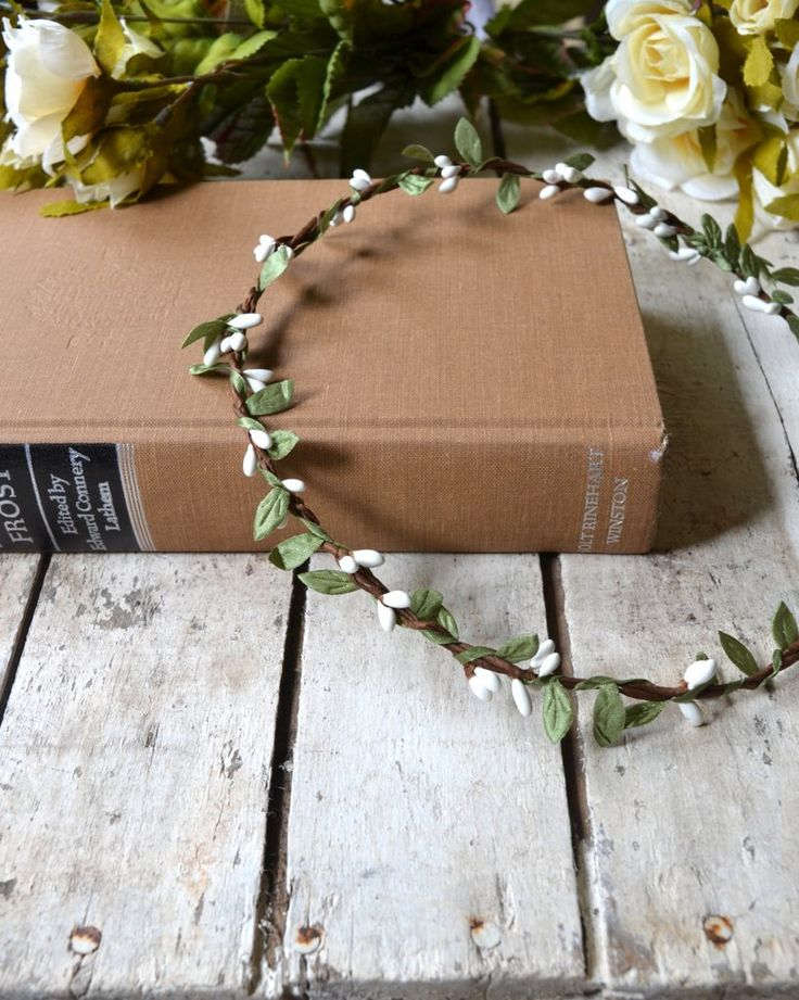 "Really pretty white flower crown. Has creamy white rosebuds with green leaves. Looks great with all of the trendy ""boho"" clothes and is fancy enough for a wedding. You can get this in child's size for"