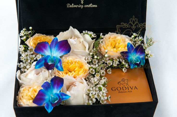 "Floral art, A luxury flower box that says ""congratulations!"" And a box of the Best Chocolate in the World Godiva"