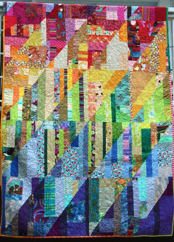 Scraps were sorted by colors of the rainbow and hue, trimmed and sewn into rectangles, rectangles were sliced diagonally, and resewn into rectangles which then were sewn into a bigger rectangle.  Then quilted.