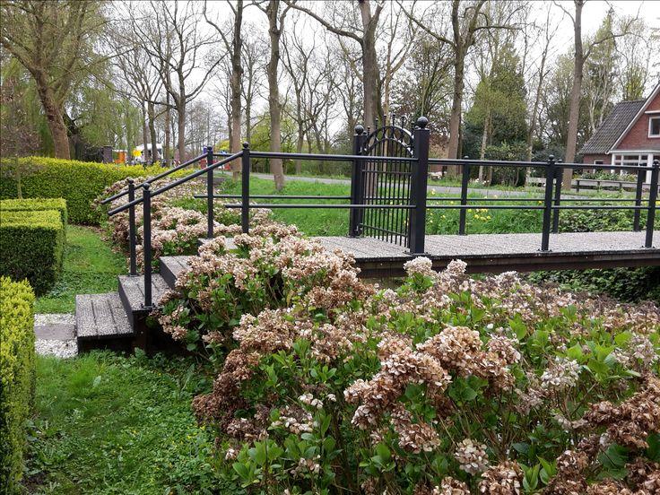 Looppoort ons model Nijenburg met robuuste 10 x 10 cm. palen met voetplaat gemonteerd op een smalle brugdek. De brugleuningen op het brugdek zijn naar wens van de klant gemaakt.