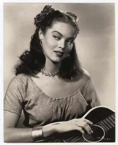 Mexican look with Spanish guitar, flowers in her hair and off the shoulder blouse, 1940s