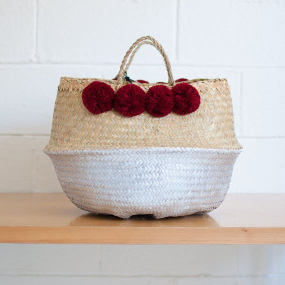 100% natural seagrass baskets, hand woven by people of a small village near my hometown of Southern Vietnam. They are flexible, foldable in half, yet incredibly sturdy for variety of uses.  Beautiful Merlot color Pom poms are hand made by Xinh & Co. team. Hand painted by Xinh & Co. Large: 14Height-17 Largest Diameter  Note: Due to handmade nature, dimension and colors of each baskets are slightly different. No two are exactly alike.  Please allow 10 business days for the package to be...