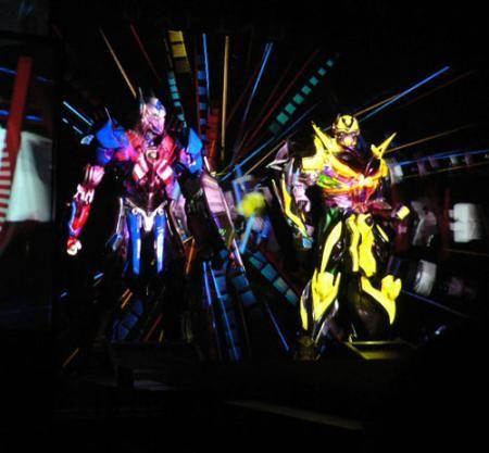 トランスフォーマー ロストエイジがプロジェクトマッピングでお披露目!! 劇中に登場するロボット「オプティマスプライム」と「バンブルビー」の立像やスクリーンに映像を当てて、実際にロボットが車から人型へ変形するように見せる、プロジェクションマッピングがお披露目された。