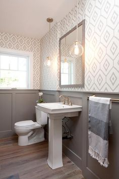Gray wainscoting lines wall covered in white and gray diamond print wallpaper holding a gray wash wood mirror flanked by clear glass globe pendants hung over a ceramic pedestal wash basin fitted with a satin nickel vintage faucet as sunlight streams in from a single hung window lighting gray wash wood floors.