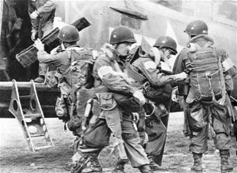 "82nd Airborne Division paratroopers check their equipment before boarding a C-47 bound for Drop Zone ""T"" near St. Mere Eglise in Normandy on D-Day, June 6, 1944."