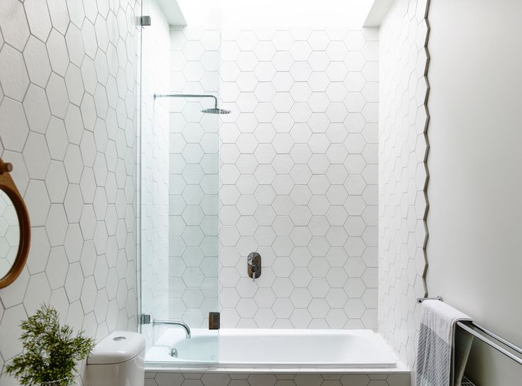 Small bathroom: white hexagon tiles with dark grey grout; shower over bath