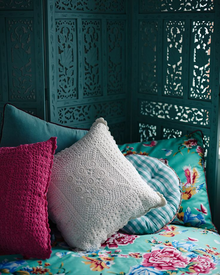 Create your own secret escape with Carolyn Donnelly Eclectic's crochet and gingham pillows and tropical-inspired floral bedspread