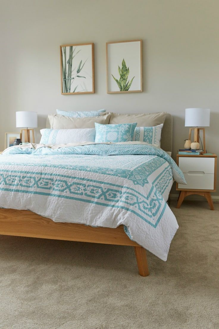mint and white bedding in master bedroom with plant art above bed