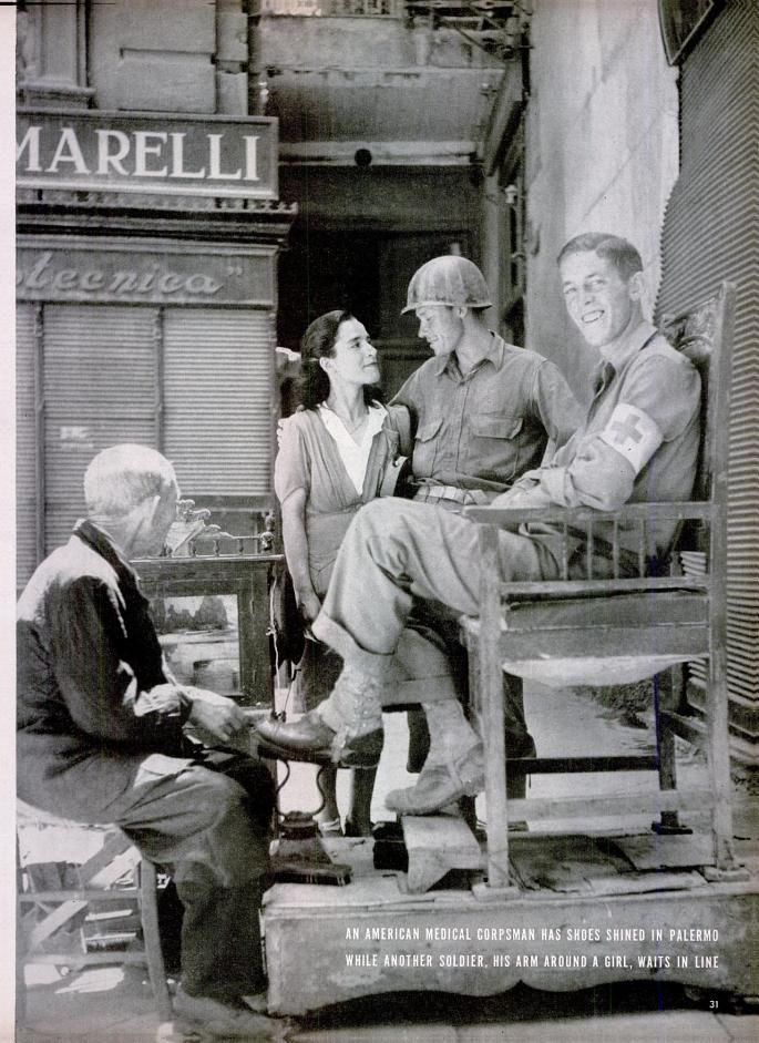 A U.S. medic gets his shoes shined in Palermo, August, 1943. Photo by Robert Capa.