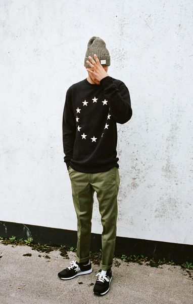 Grey beanie, star graphic black sweatshirt, skinny khakis and black trainers. | More outfits like this on the Stylekick app! Download at http://app.stylekick.com