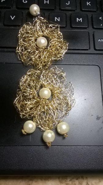 Brinco tramado com fio de cobre com leve banho de ouro medindo aproximadamente 10 cm e comprimento por 5 cm de largura e pérolas artificiais. Gancho em aço cirurgico. Totalmente leve e feito a mão. SOMENTE SOB ENCOMENDA! Tempo de confecção: m...