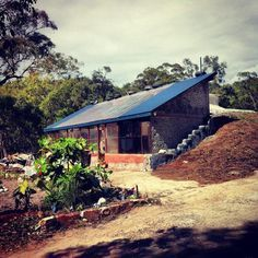 picture of first earthship built in australia. hempcrete roof, tyre walls, bottle walls, can walls, clay plaster